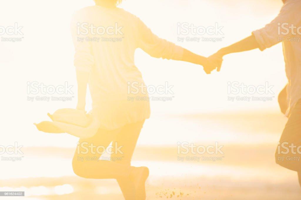 Paar entlang des Strandes Händchenhalten bei Sonnenaufgang oder Sonnenuntergang. – Foto