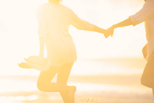Couple running along the beach holding hands at sunrise or sunset. stock photo