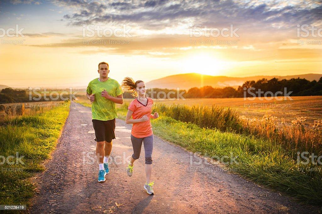 Couple running at sunset stock photo