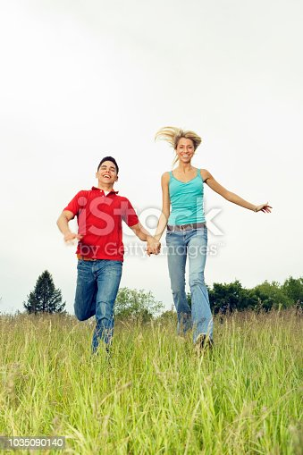 1083155024 istock photo Couple running in meadow 1035090140