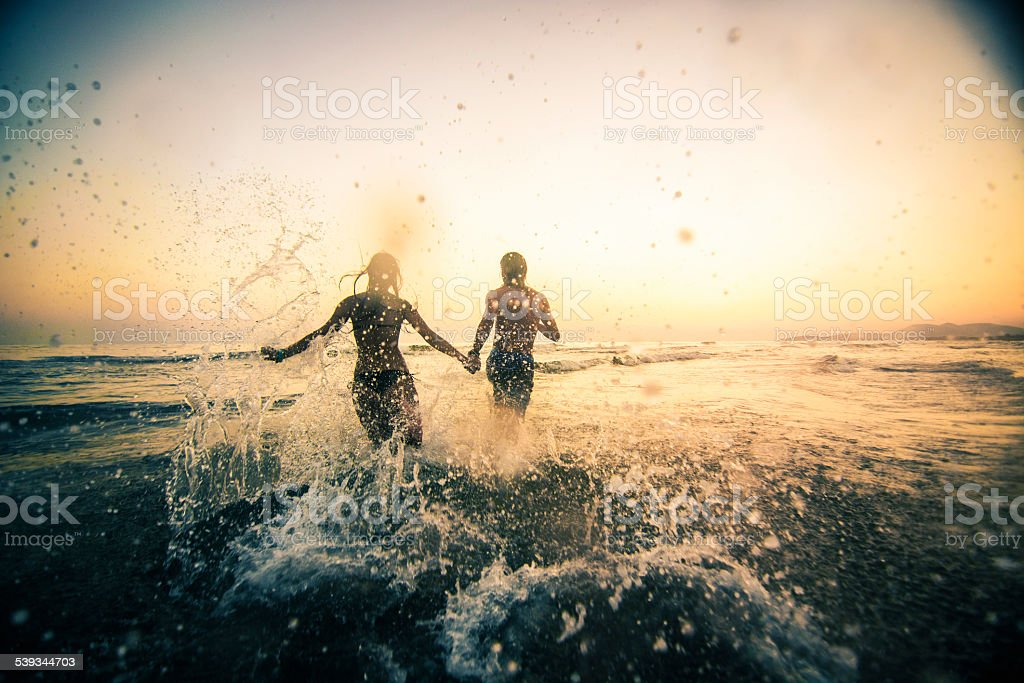 Couple running in the sea stock photo