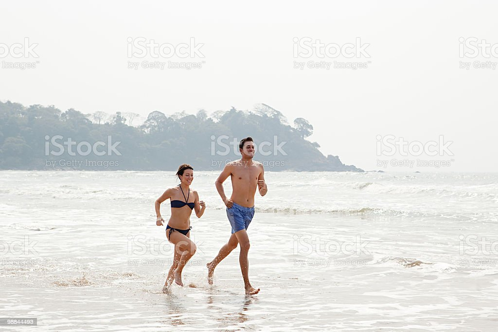 Couple running in the sea royalty-free stock photo