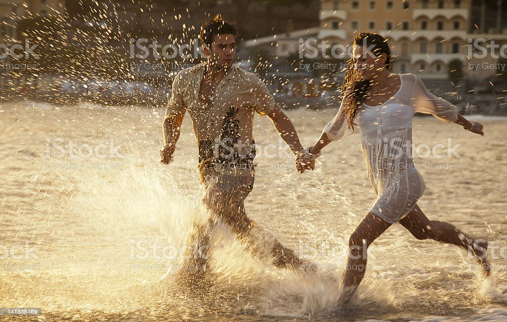 Couple running in waves at beach stock photo