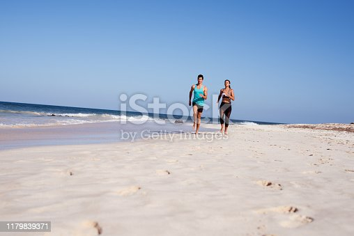 Long distance shot of a young couple jogging together on a white sandy beach