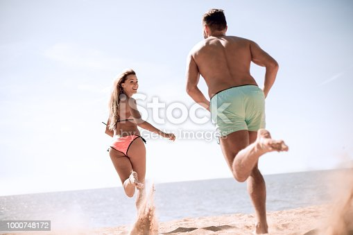 Happy lovers playing with each other on the beach.