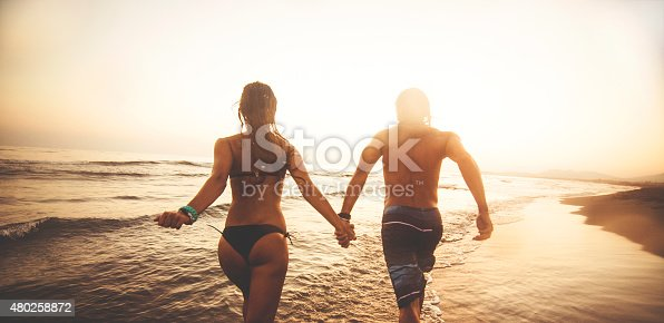 Silhouette of couple in love running on the beach and holding hands.