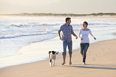 Young couple running on the beach with their dog