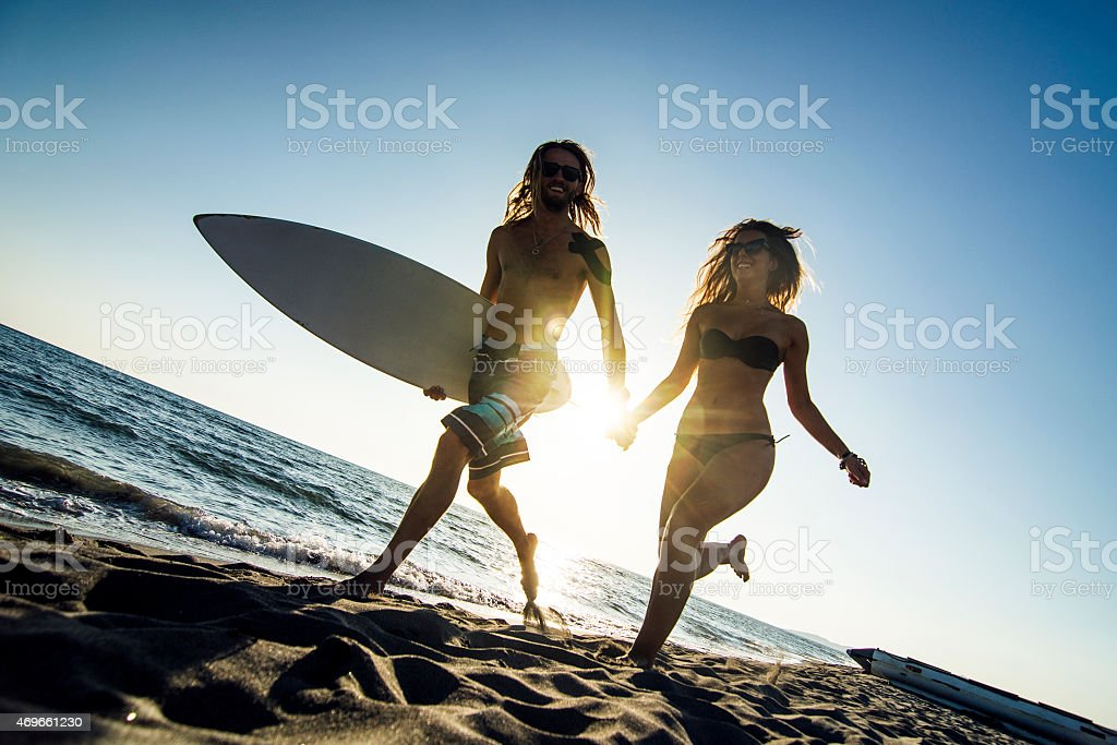 A couple running on the beach while carrying a surf board stock photo