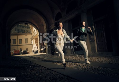 couple running thru an ominous street tunnel in small town of northern italy as someone bad was chasing them.