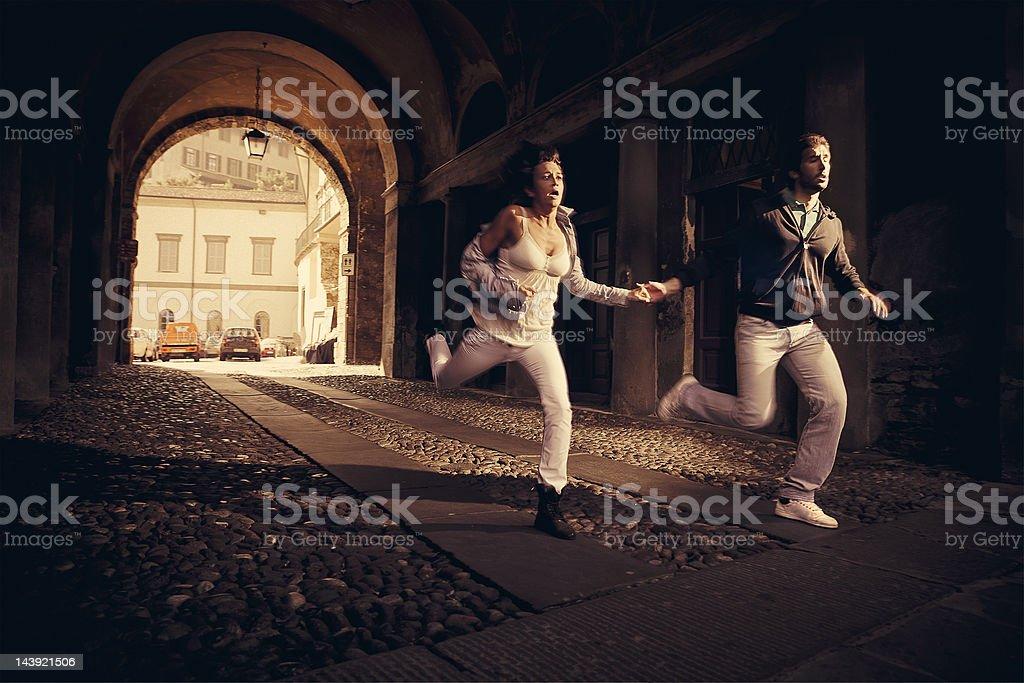couple running scare stock photo