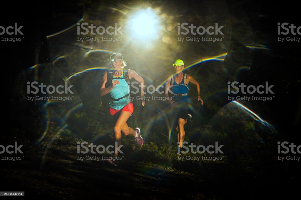 Couple running through a forest at night stock photo