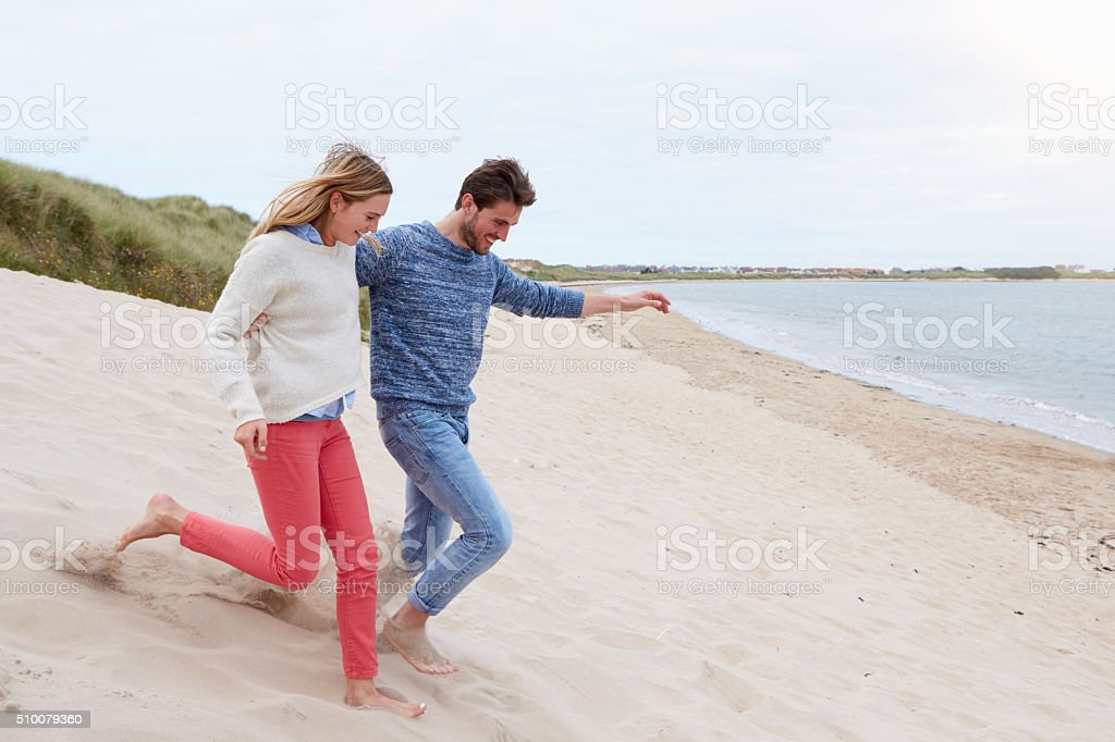 Couple Running Through Sand Dunes Together stock photo