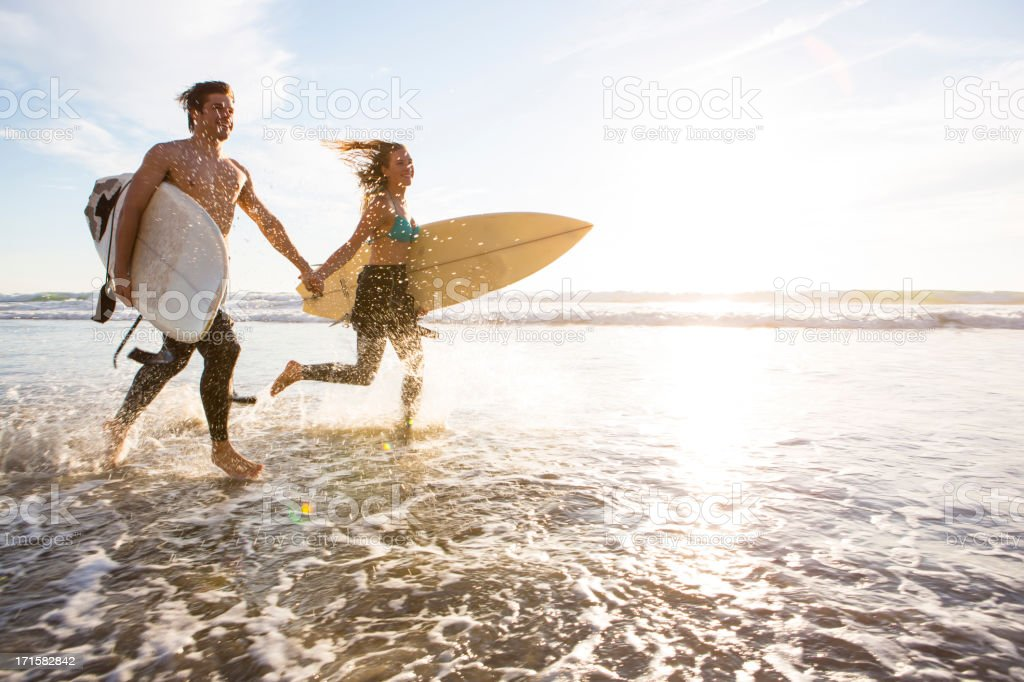 Couple running through the surf stock photo
