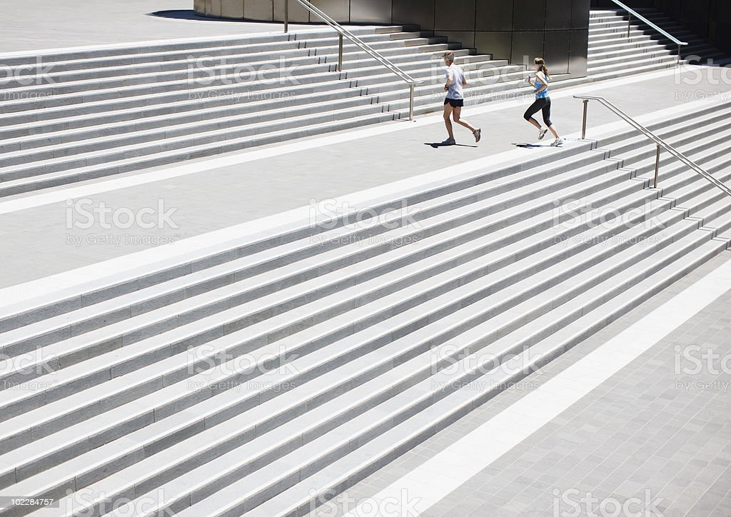 Couple running up urban staircase royalty-free stock photo