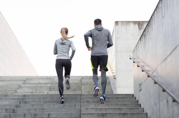 couple running upstairs on city stairs stock photo