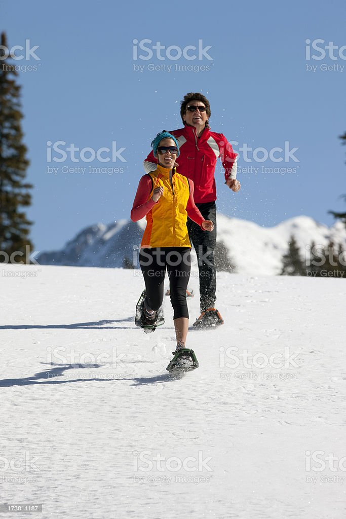Couple running with snowshoes on royalty-free stock photo