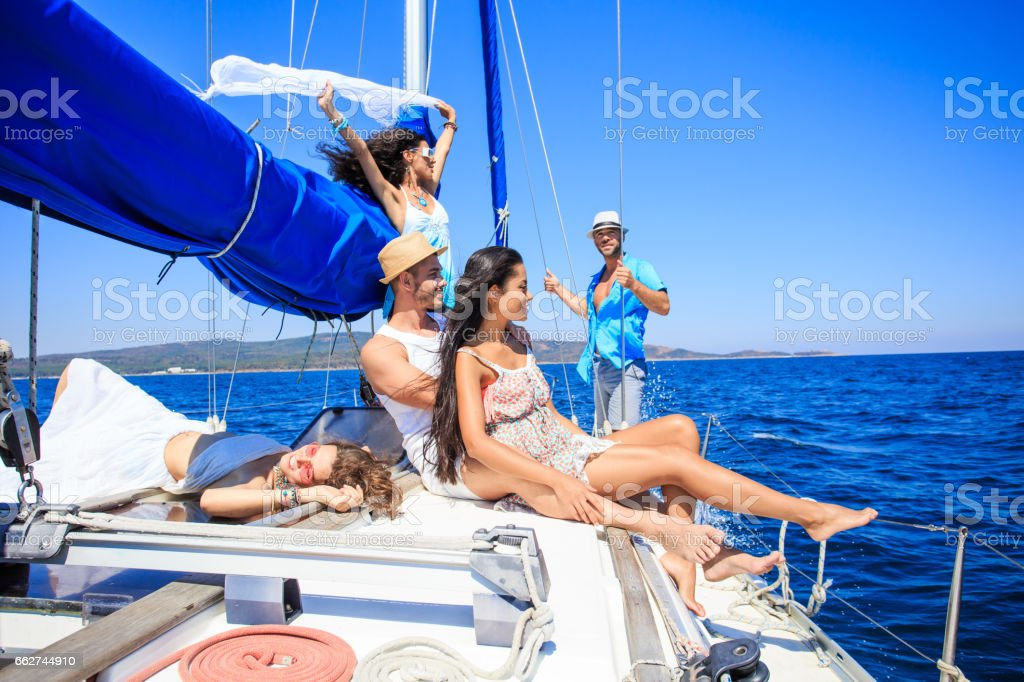 Couple sailing with friends stock photo