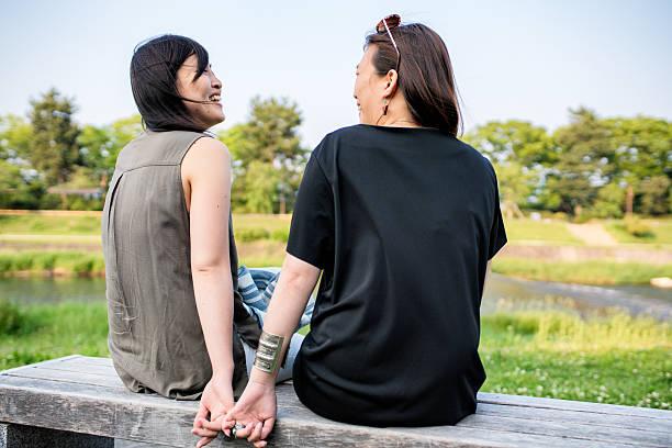 lgbt couple sat lovingly together - lgbtqi  ストックフォトと画像