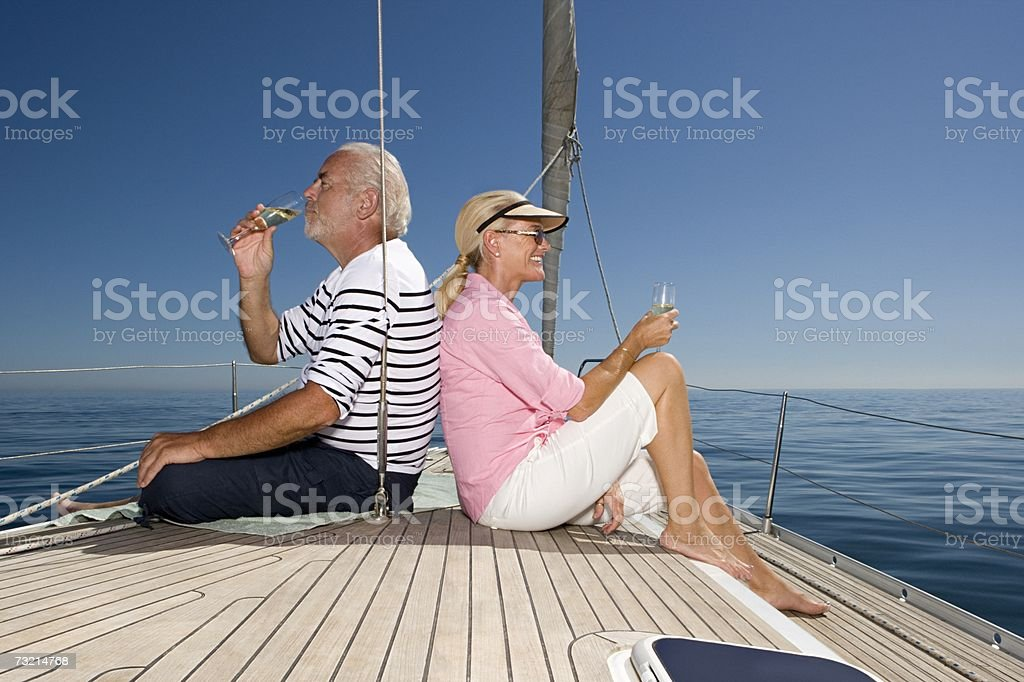 Couple sat on sailboat with champagne stock photo