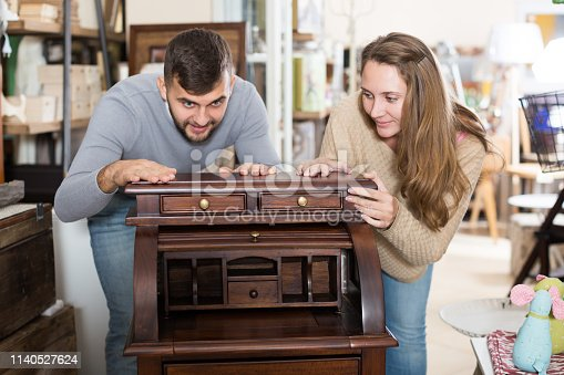 Loving couple satisfied with purchase of old stylish writing cabinet at home