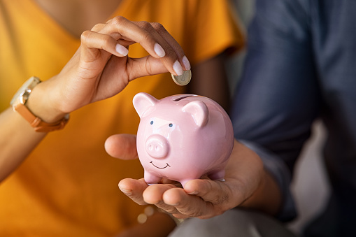 Close up of man holding pink piggybank while woman putting coin in it. Indian young couple saving money for their wedding. Close up of woman hand putting euro money in piggy bank to save for the purchase of an house.