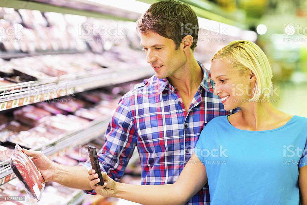 Couple Scanning Product Using Bar Code Reader In Smart Phone royalty-free stock photo