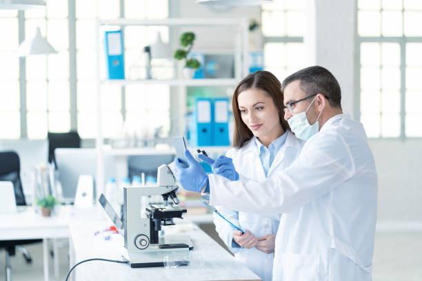couple scientists in laboratory - pharmaceutical factory stock pictures, royalty-free photos & images
