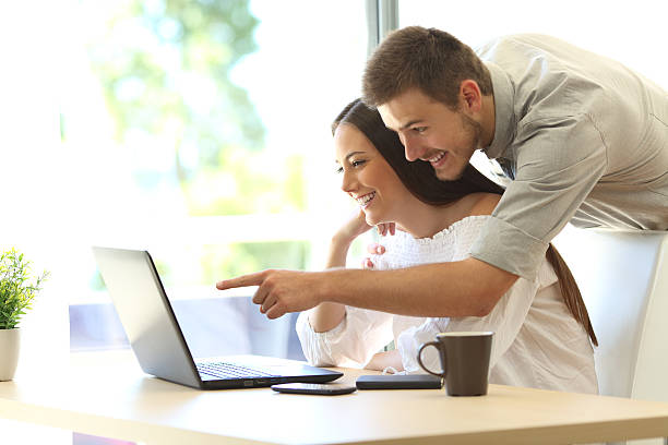 couple searching online in a laptop at home - suche freundin stock-fotos und bilder