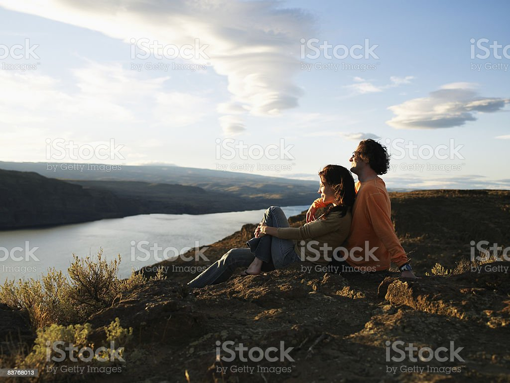 Couple seated above river gorge watching sunset royalty-free stock photo