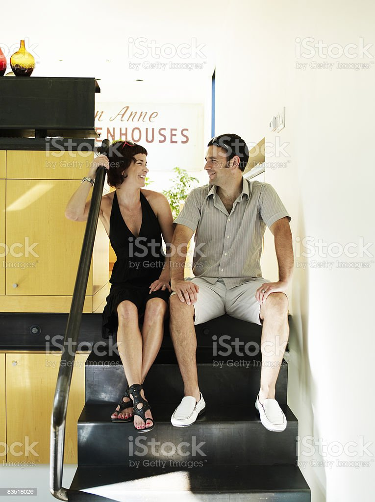 Couple seated on interior steps of home, laughing royalty free stockfoto