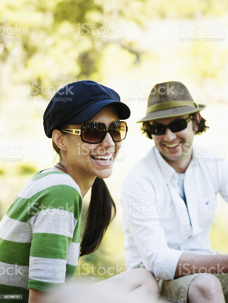 Couple seated outdoors, laughing royaltyfri bildbanksbilder