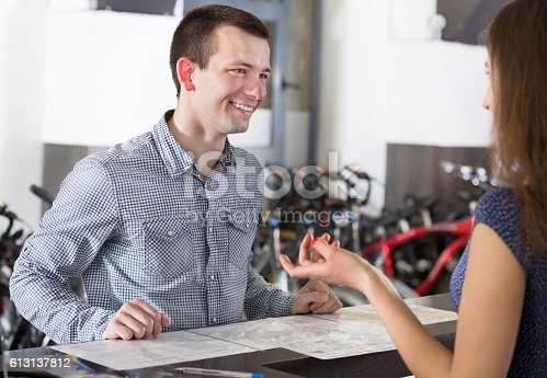 istock Couple selecting bikes at rental agency 613137812