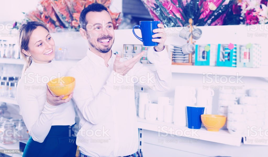 Couple selecting crockery in store stock photo