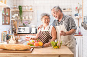 Couple senior Asian elder happy living in home kitchen. Grandfather cooking salad dish with grandmother with happiness and smile enjoy retirement life together. Older people relationship and activity.