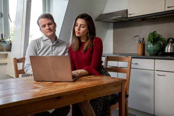 Couple seriously looking at a laptop at the dining table stock photo