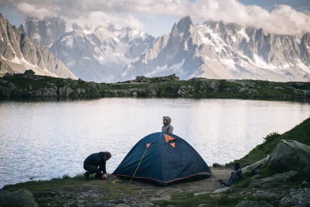 paar aufgesiebten zelt im camp am bergsee - zelt stehhöhe stock-fotos und bilder