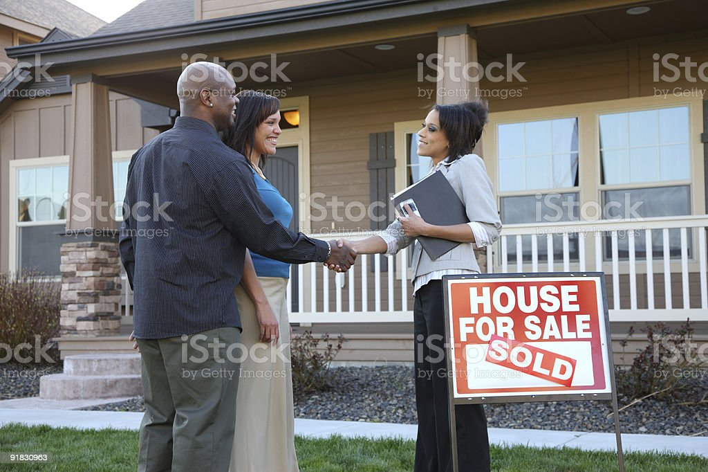 Couple shakes hands with realtor outside new house stock photo