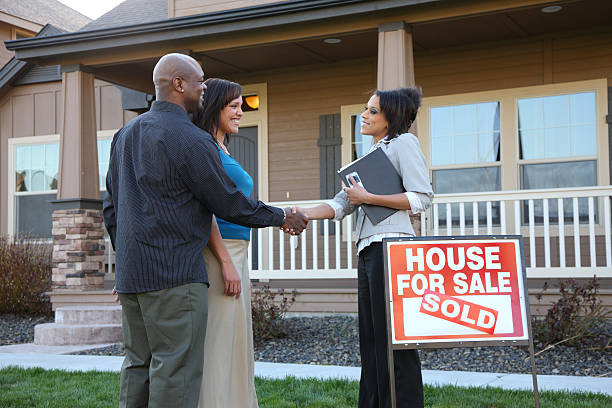 couple shakes hands with realtor outside new house - estate agent sign stock photos and pictures