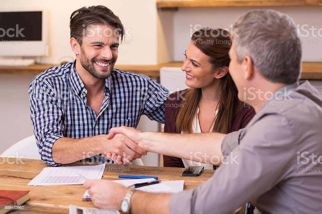 Couple shaking hand to financial agent stock photo