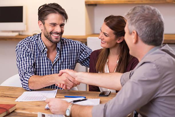 Couple secousse de main à agent financier - Photo