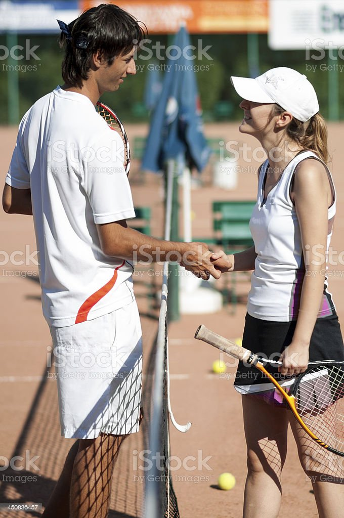 couple shaking hands after tennis match royalty-free stock photo