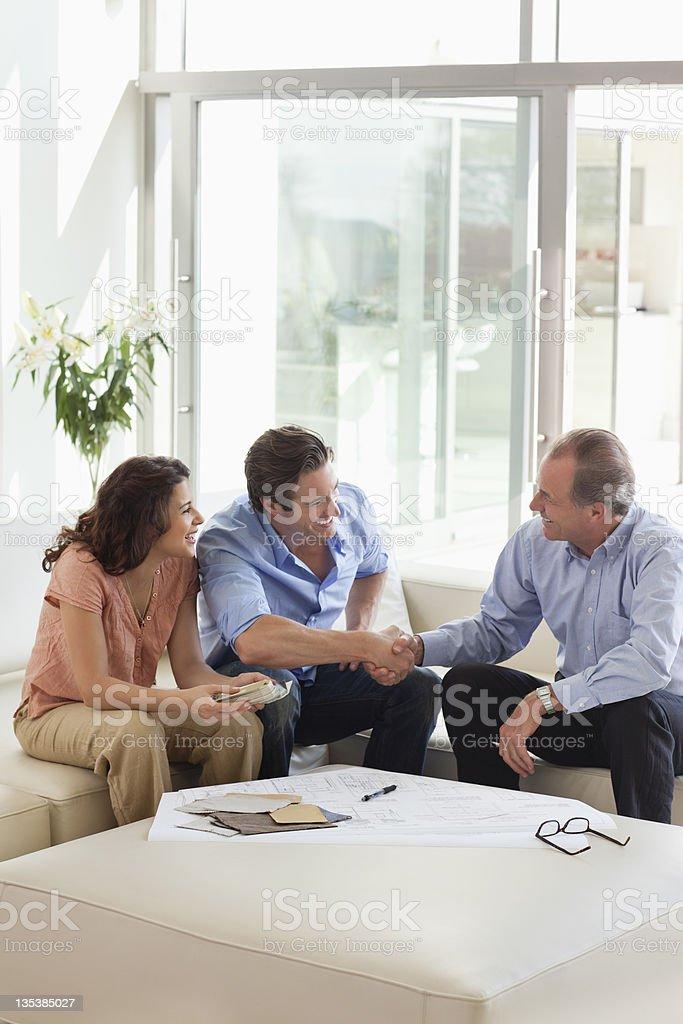 Paar beim Händeschütteln mit financial advisor – Foto