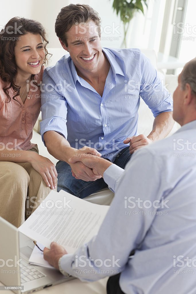 Couple shaking hands with financial advisor royalty-free stock photo