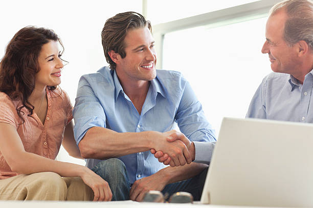 couple shaking hands with financial advisor - financial advisor with clients stock photos and pictures