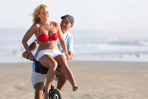 couple share a bicycle - older women bikini stock pictures, royalty-free photos & images