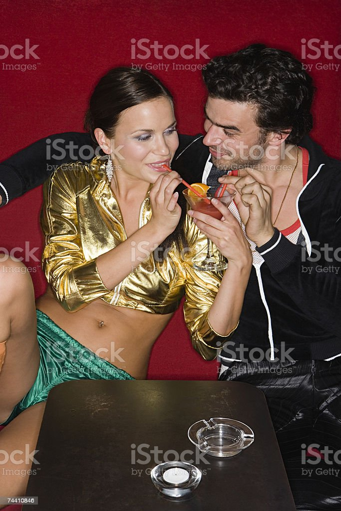 Couple sharing a cocktail royalty-free stock photo