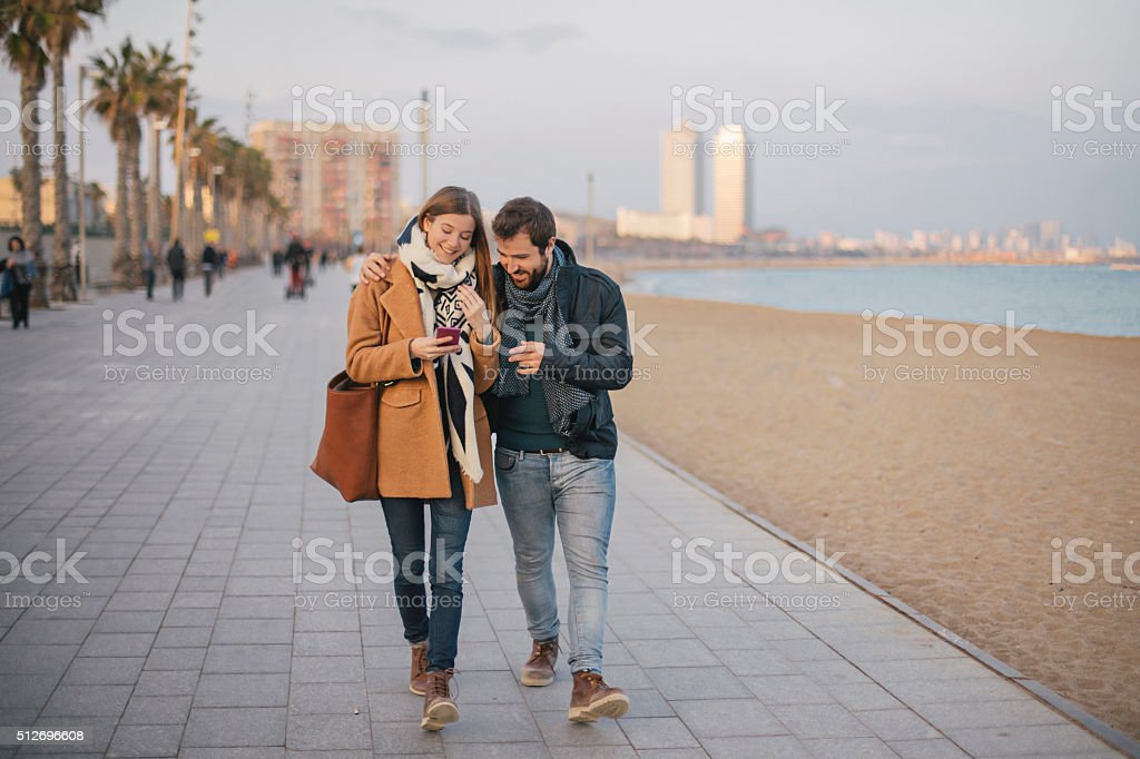 Couple sharing a message on the smart phone stock photo