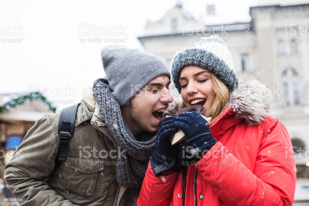 Couple sharing chocolate donut at Christmas market stock photo
