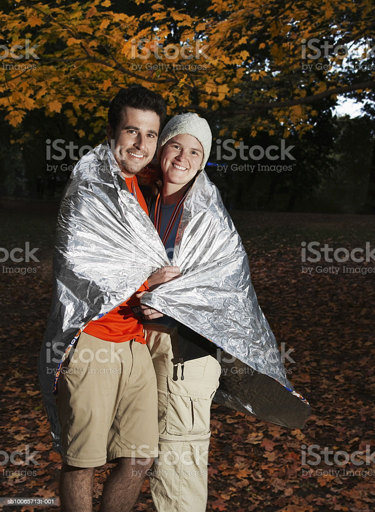 Couple sharing silver blanket, smiling, portrait royalty-free stock photo