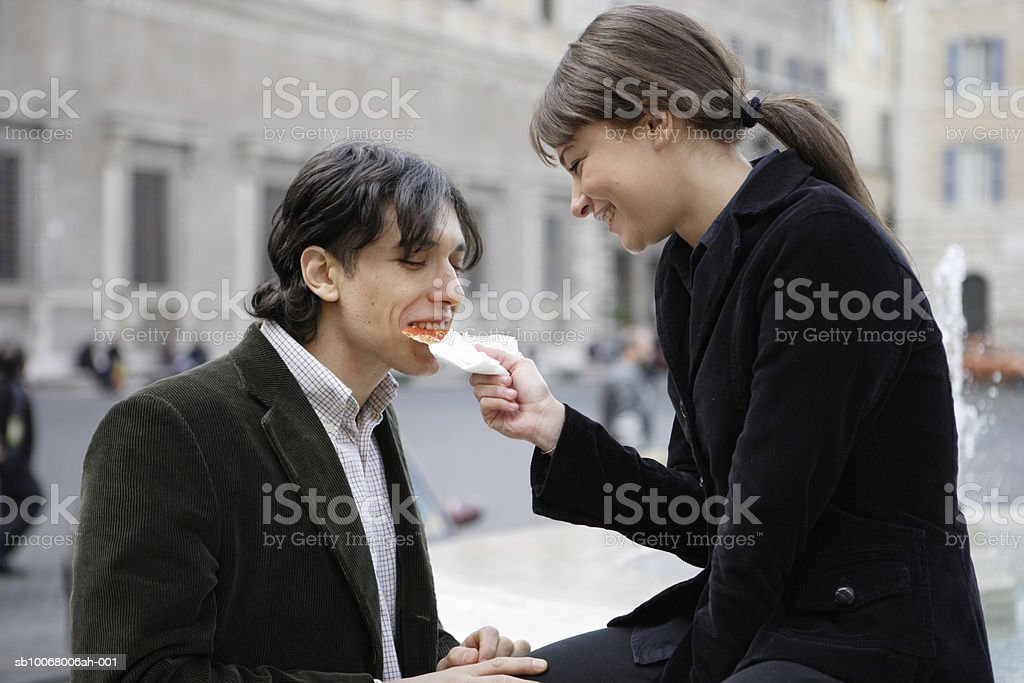 Couple sharing slice of pizza outdoors royalty free stockfoto